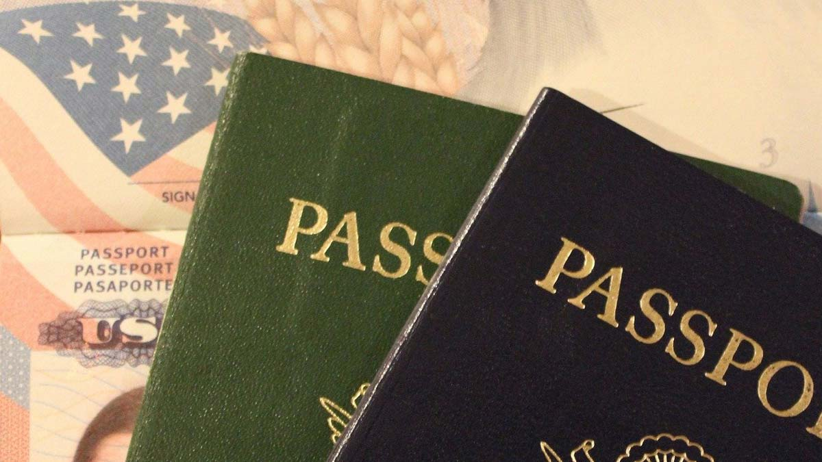 Photo of two passport books with American flag image in background